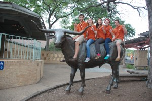 5 UT students sitting on top of Longhorn statue