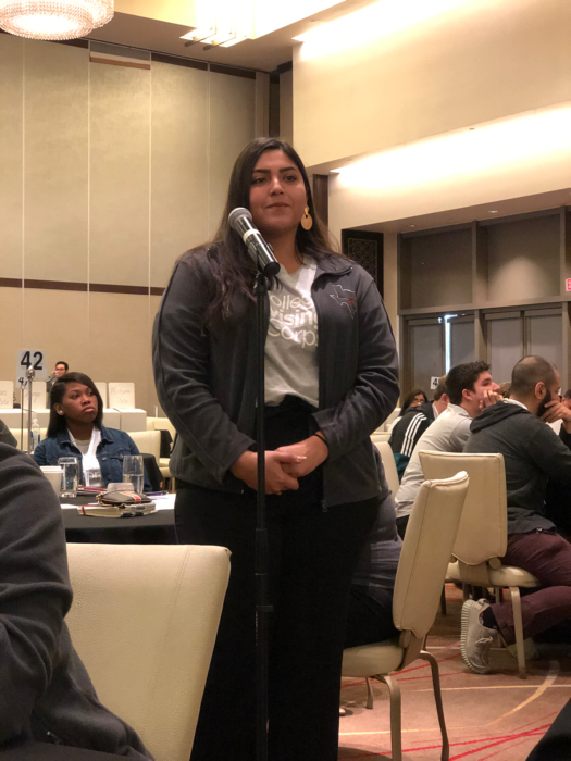 Juliann Solis asking a question during a luncheon session