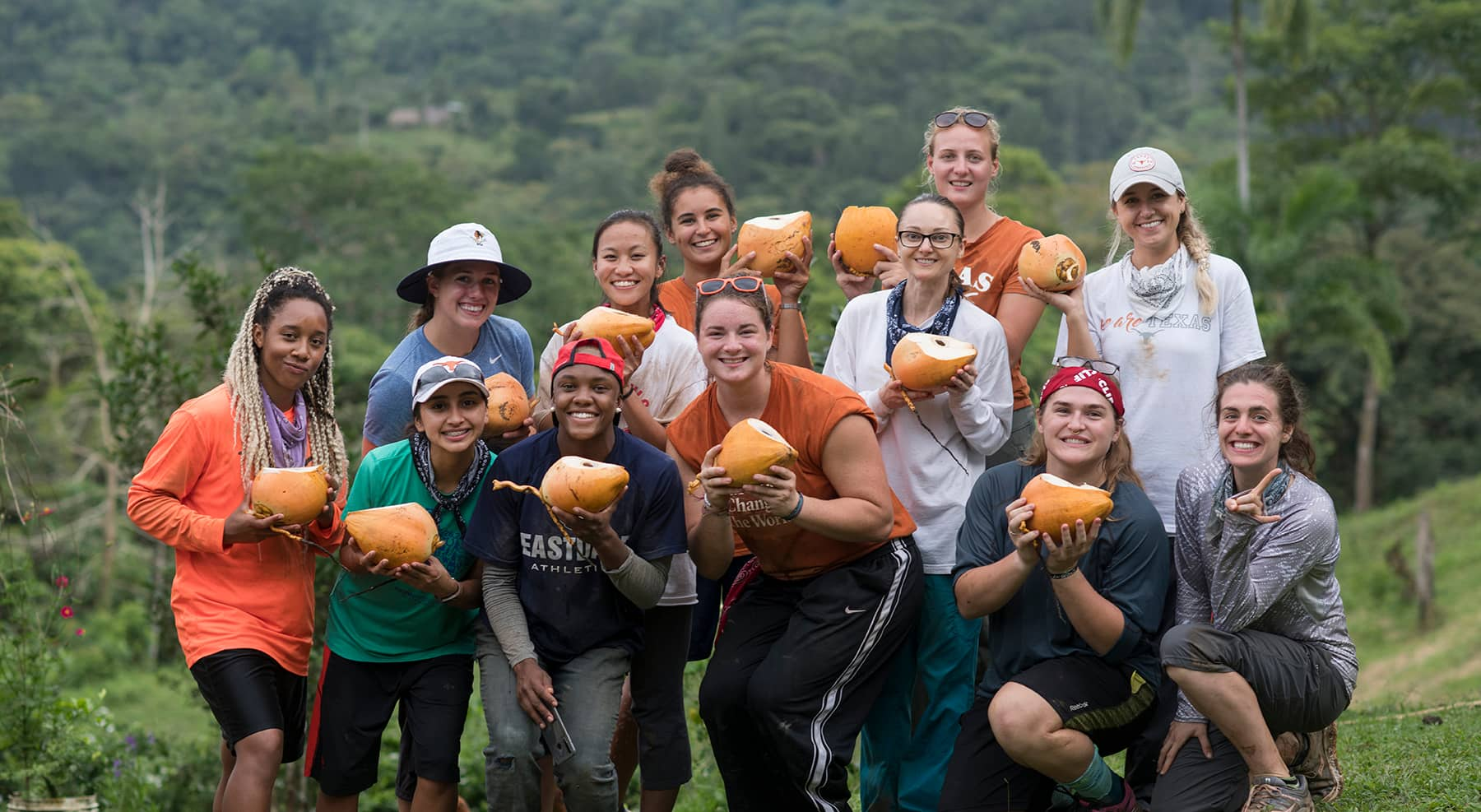 Group of students holding up coconuts