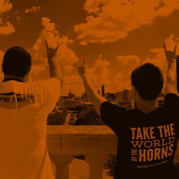 Two UT Austin First-Gen students holding up Hook'em Horn hand sign looking out over the Texas Capital