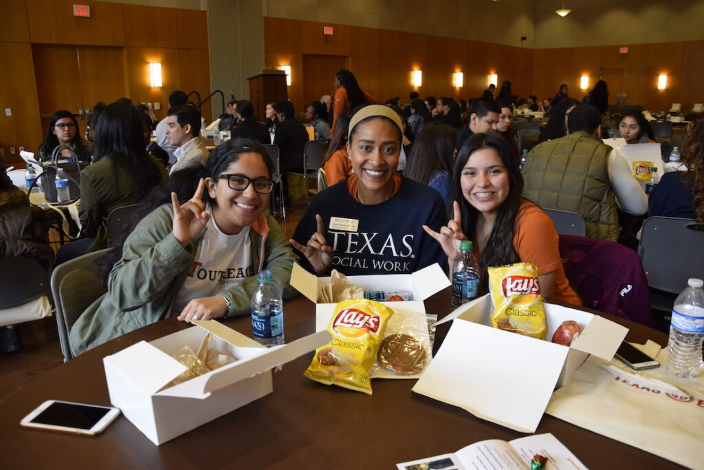 YEC students smile for the camera during a lunch networking session with UT Austin professors