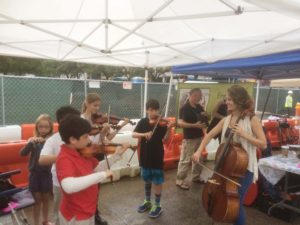 Kids playing violins.